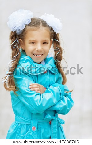 Little smiling beautiful girl with bows in blue cloak.