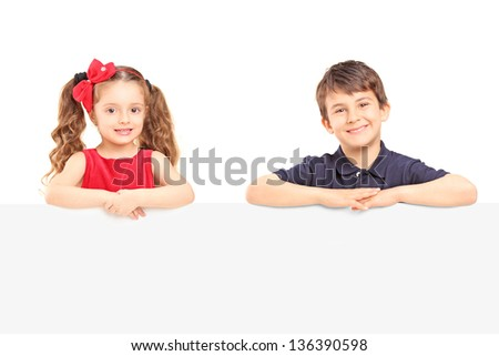 Little smiling boy and girl standing behind a blank panel isolated on white background