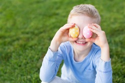 little smiling boy being playful at spring time covering his eyes with colorful easter eggs after egg hunt in the park