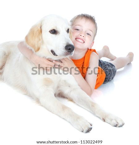 Little smiling boy hugging a dog on white background