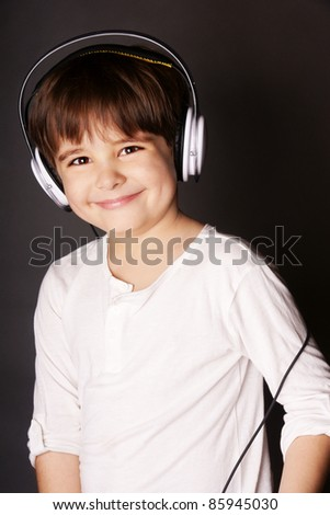 Little smiling boy in striped shirt and headphone listening to music, studio shot