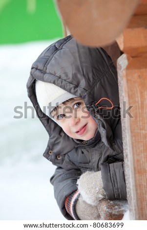 little smiling boy in the warm winter clothes on outdoors