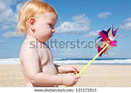 Little smiling boy is holding a pinwheel in front of the cloudy sky.