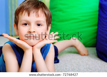 Little smiling boy is playing on a floor at home.