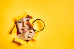 Little smiling caucasian boy looks through torn hole in paper yellow wall, holding magnifying glass in his hand. Search, discovery, research concept. Sidebar for text information, advertising, event.
