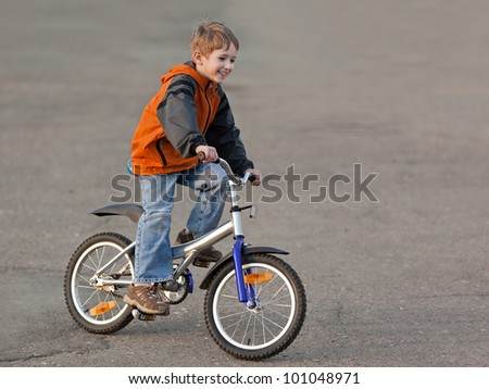 Little smiling child boy cycling sport bicycle outdoor - stock photo