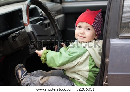 Little smiling child boy driving sport car vehicle - stock photo