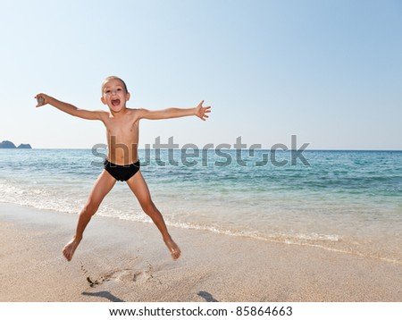 Little smiling child boy jumping on sea sand beach #85864663