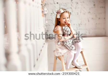 little smiling cute girl in beautiful dress is sitting with teddy bear in her hands #259300421