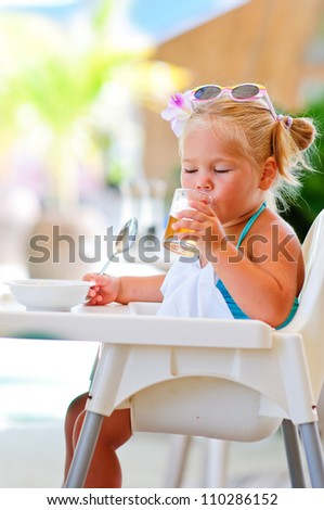 little smiling girl have a breakfast in outdoor cafe and drinking fresh juice
