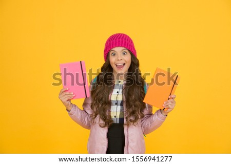 Little smiling girl hold books. Future textbooks modern education. Textbook useful in learning environment. School creating textbooks generation. Active role in curriculum. Schoolgirl with textbooks.