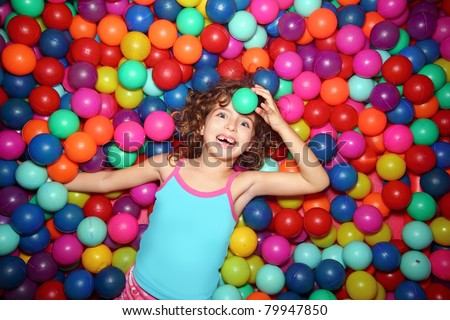 little smiling girl playing lying in colorful balls park playground