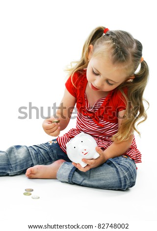 Little smiling girl playing with a piggy bank and money