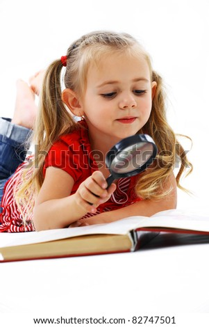 Little smiling girl reading a book with a magnifying glass