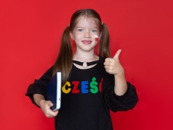 little smiling girl  showing thumbs up, holding a book in her hands. on her sweatshirt the word Hello in Polish, the advertising concept of the Polish school, the study of the Polish language