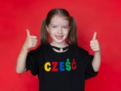 little smiling girl showing thumbs up , on her sweatshirt the word Hello in Polish, the advertising concept of the Polish school, the study of the Polish language