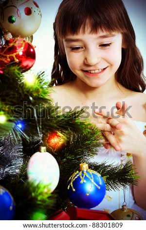 Little smiling girl under a Christmas tree. Looking at Christmas-tree decoration