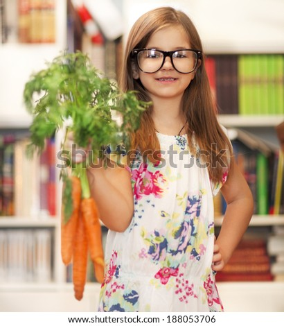Little smiling girl wearing glasses with bunch of organic carrots