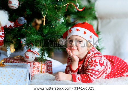Little smiling girl wearing Santa hat and festive dress lying on the lambskin carpet near the Christmas tree and gifts. Adorable kid making new year wishes.