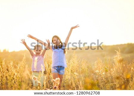Little smiling girls stand on sunshine evening field with joyfully raised hands #1280962708