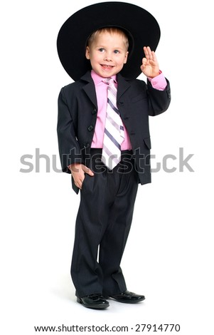 Little smiling saluting boy in stylish black suit