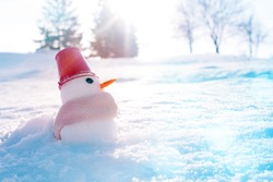 Little snowman with a red decorative bucket on his head and wrapped in a scarf in the snow on a winter sunny day, closeup, soft focus. Symbol of winter, new year, christmas background