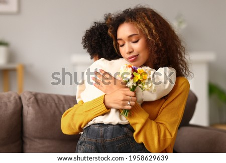 Little son congratulating mom with Mothers day at home and giving her fresh flower bouquet, happy mixed race woman mother embracing son while sitting on sofa. Family holidays and celebration concept