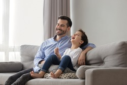 Little son sit on couch with father different age men laughing spend time watching comedy movie, cartoons feels happy, activities with kid at home, best friends, warm relations funny weekends concept