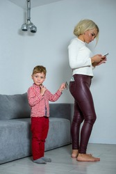 Little son steals money from mom from his pocket. Mom looks at the phone while son steals money from her pocket.
