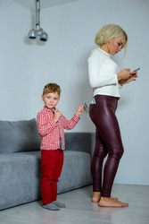 Little son thief steals money from mom pocket. While mom looks at the phone, son steals money from her pocket.