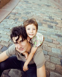 little son with father in city