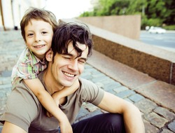 little son with father in city hagging and smiling, casual look