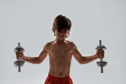 Little sportive boy child with muscular body looking emotional while exercising, lifting weights, standing isolated over grey background. Health and strength concept. Front view. Horizontal shot