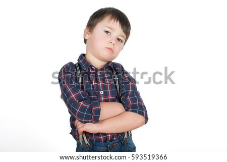 Little stubborn boy standing with crossed hands pretending he is a tough guy. Isolated on a white background.