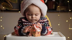 Little sulking baby boy with serious face wearing Santa hat playing with toy gingerbread house sitting in baby high chair at home. Funny baby, Christmas celebration concept.