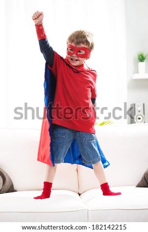 Little superhero boy standing on sofa and posing like a real hero