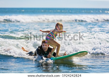 Little surf girl - young surfer learn to ride on surfboard with instructor at surfing school. Active family lifestyle, kids water sport lessons, swimming activity in summer camp. Vacation with child.