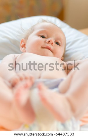 little sweet baby lying on back and playing with his feet
