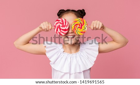 Little sweet tooth. Adorable girl covering her eyes with two colorful lollipops, pink panorama background