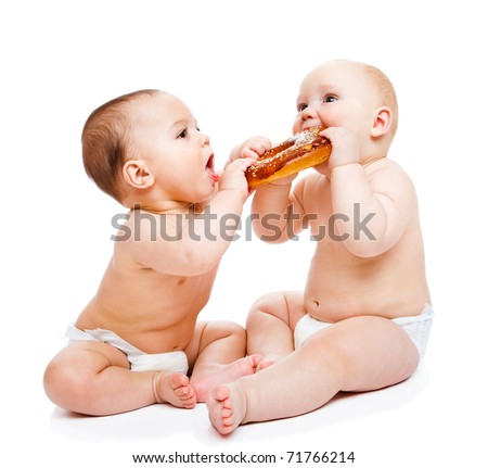 Little sweeties in diapers eating a roll - stock photo