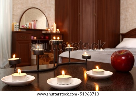 little table in a bedroom decorated with burning candles and apples