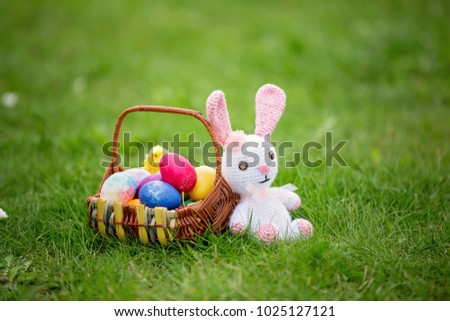 Little teddy bear toy and a basket of eggs colored for Easter holiday #1025127121