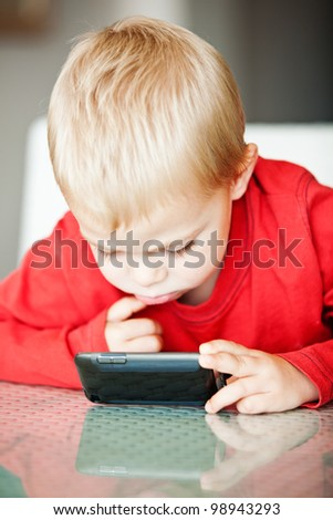 little three year old boy playing with his media player with a puzzled expression  shallow depth of field, focus on the eye