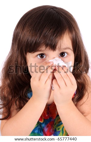 Little three year old girl having the sniffles and wiping her nose with tissue from being sick or allergies