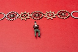 Little tiny man person figurine  and gear wheels as industry concept