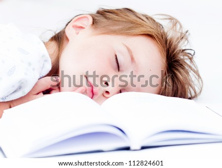 Little tired girl sleeping after reading