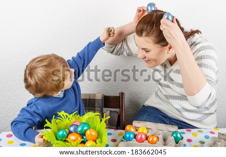 Little toddler boy and his mother having fun with preparing eggs for Easter egg hunt, traditional action in Germany for Eastern holiday, indoors