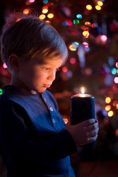 Little toddler boy holding candle with colorful lights from Christmas tree on background.