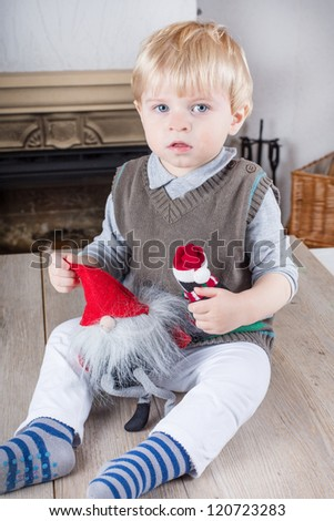 Little toddler boy playing with Christmas toys