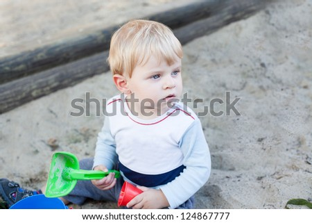 Little toddler boy playing with sand and toy on playground in summer